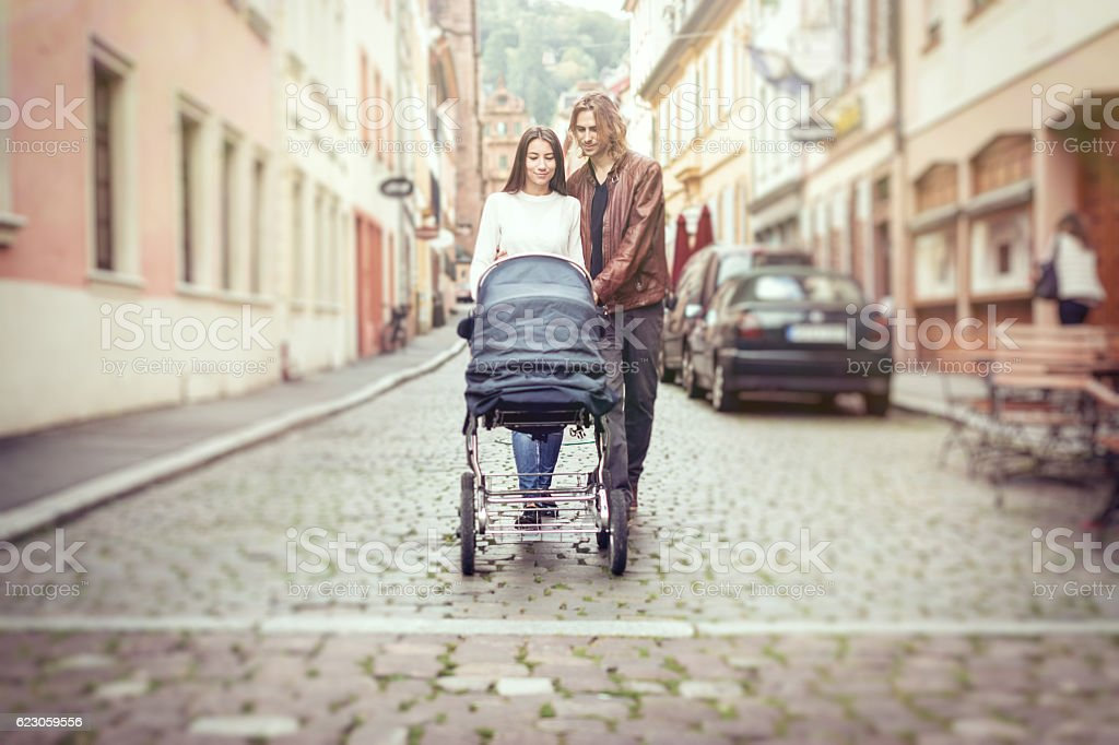 Young parents with baby stroller in the city stock photo