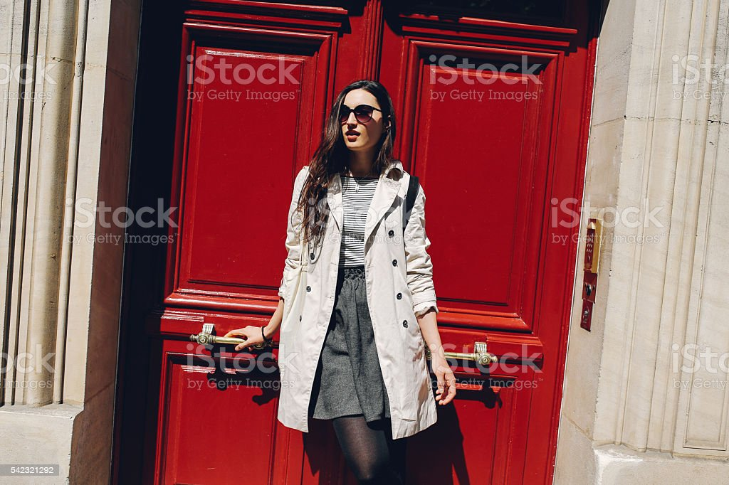 Young Parisian woman in font of her apartment stock photo
