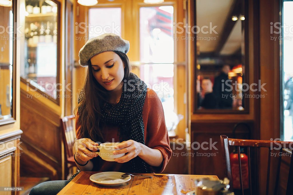 Young Parisian woman sitting in a cafe stock photo
