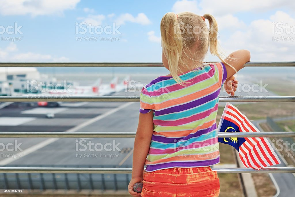 Young passenger looks at planes in airport stock photo
