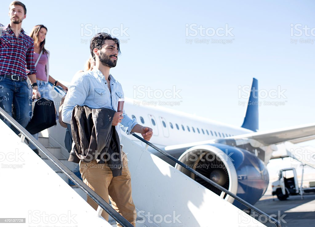Young passengers getting out of the airplane. stock photo