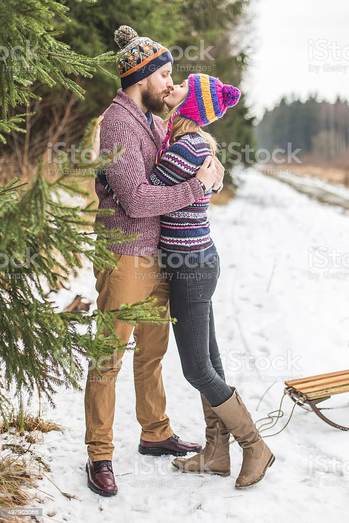 Young peaople are kissing in winter forest stock photo