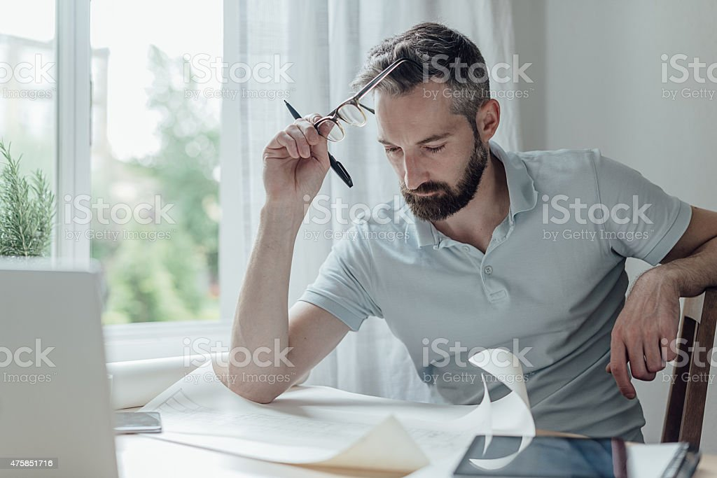 young pensive architect looking on plan at desk holding glasses stock photo