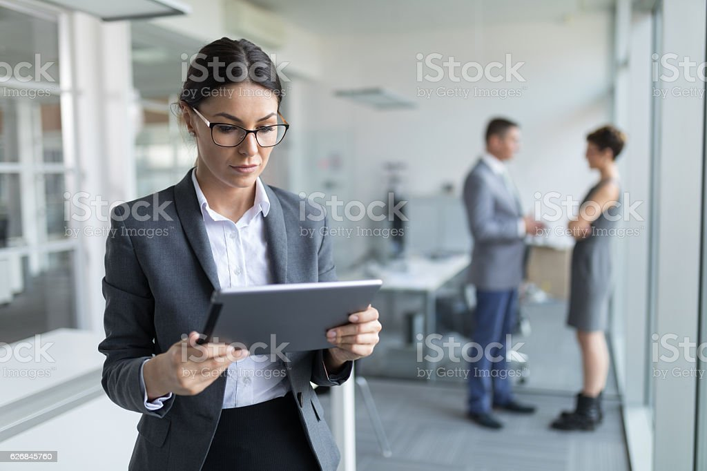 Young pensive  businesswoman using digital tablet in the office stock photo