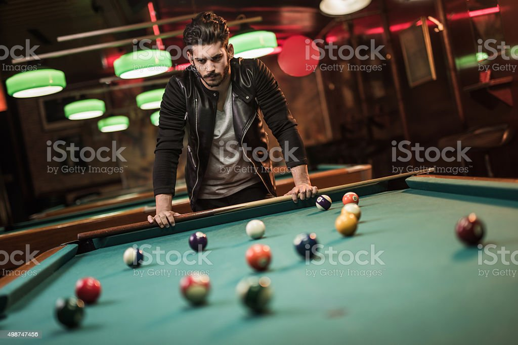 Young pensive man thinking of his next billiard move. stock photo