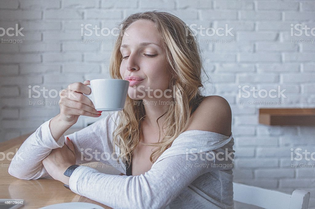 Young pensive woman at cafe enjoying fresh cup of coffee stock photo