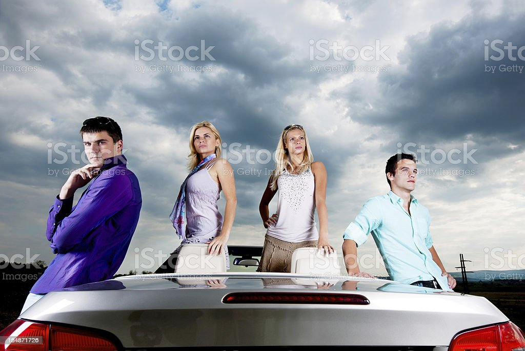 Young people and Convertible car against sky. royalty-free stock photo