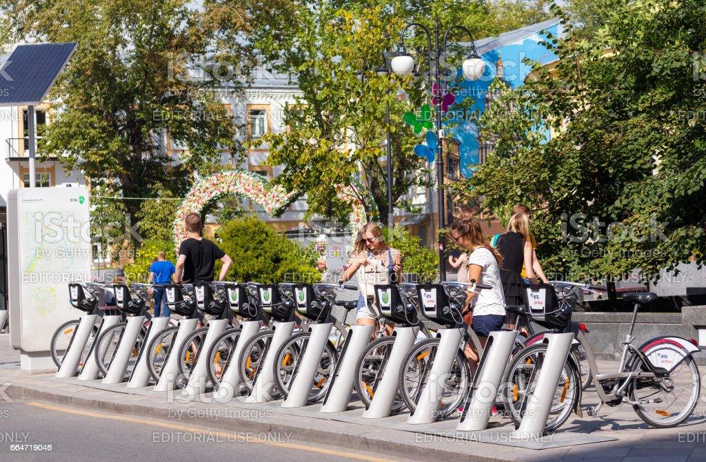 Young people at bicycle rental station on Pyatnitskaya street in Moscow stock photo