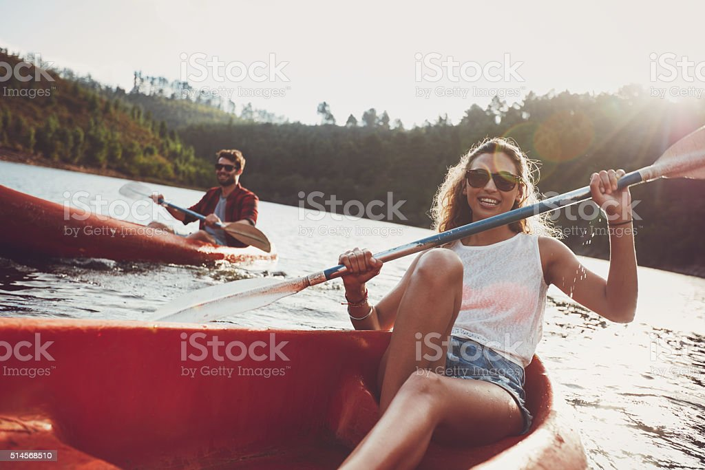 Young people canoeing in a lake stock photo