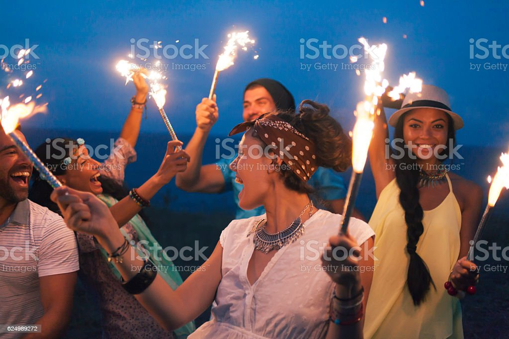 Young people celebrating with fireworks on beach stock photo