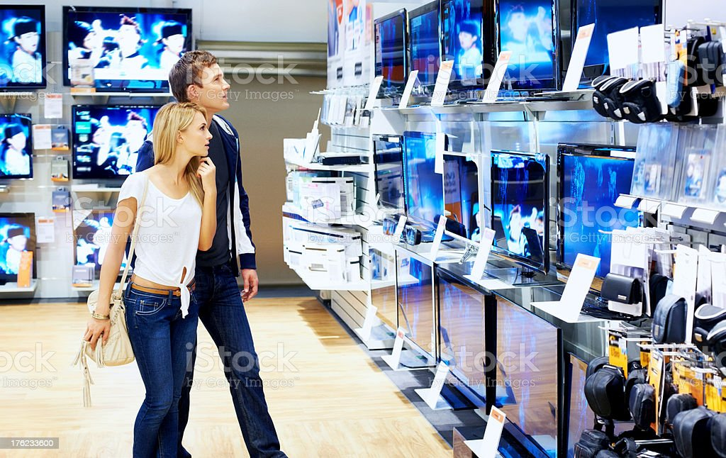 Young people checking out new television sets in megastore stock photo