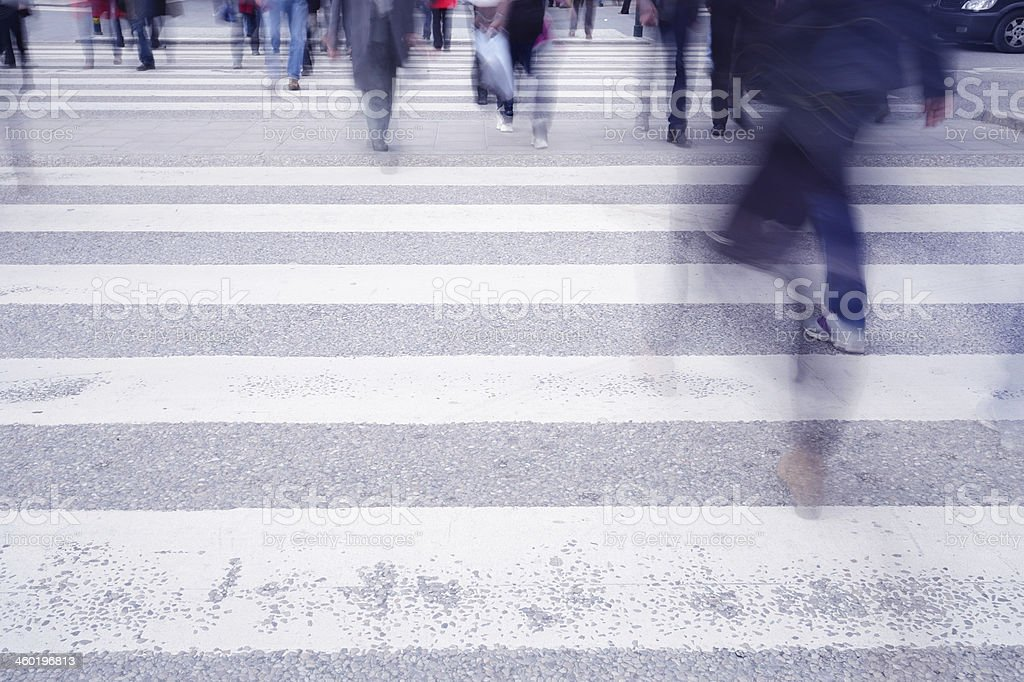 Zebra crossing with motion blurred people crowd.