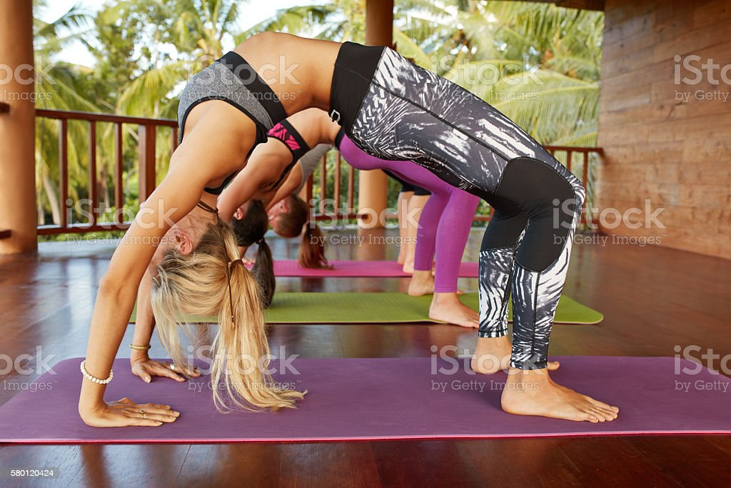 Young people doing Chakrasana yoga stock photo