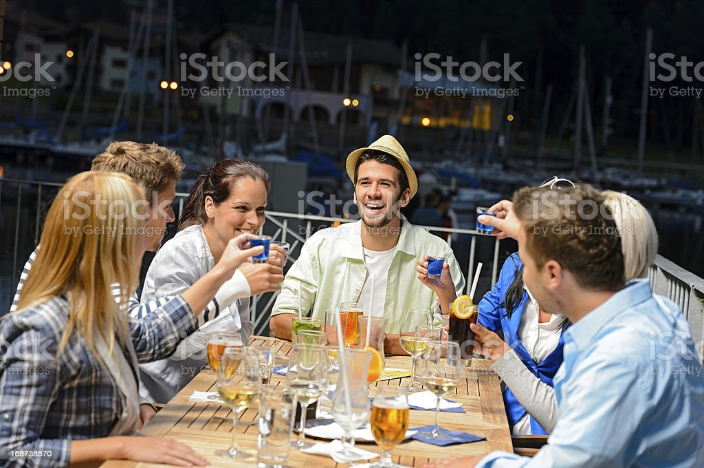 Young people doing shots at outside bar stock photo