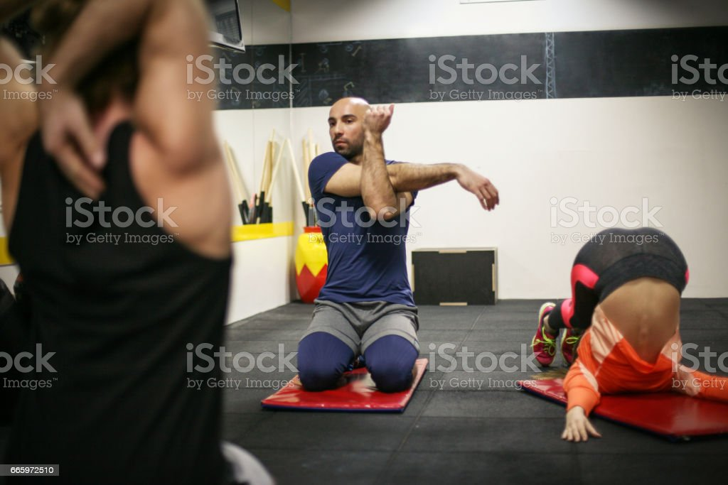Young people doing stretching exercise in school gym. stock photo