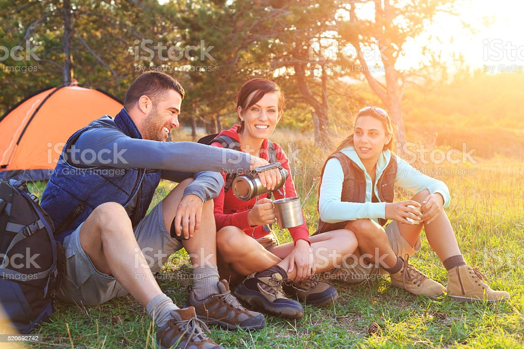 Young people drinking coffee in front of their tent stock photo