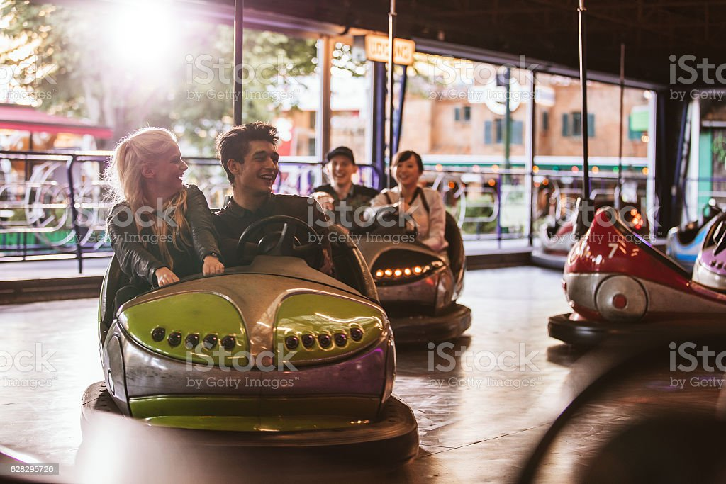 Young people driving bumper car at amusement park stock photo