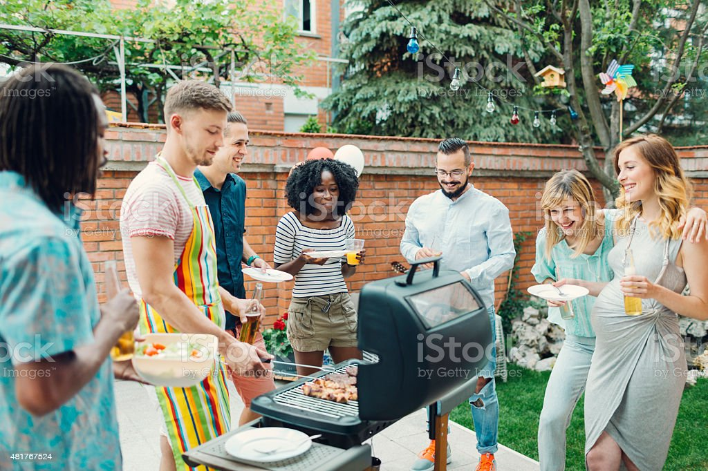 Young People Eating At Barbecue Party. stock photo