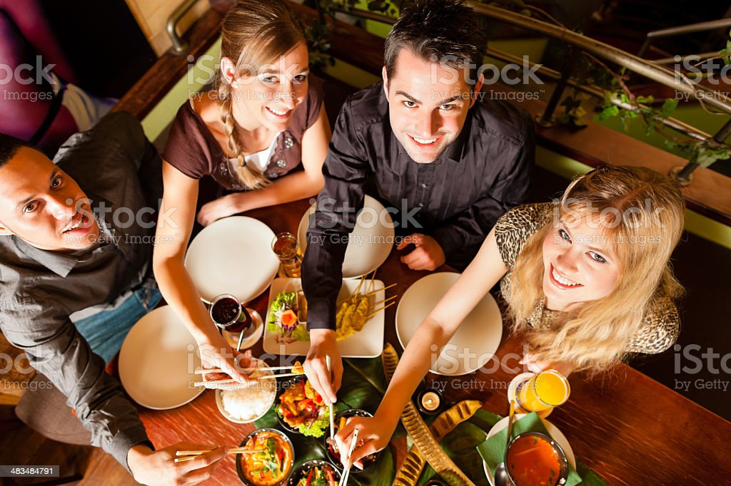 Young people eating in Thai restaurant stock photo