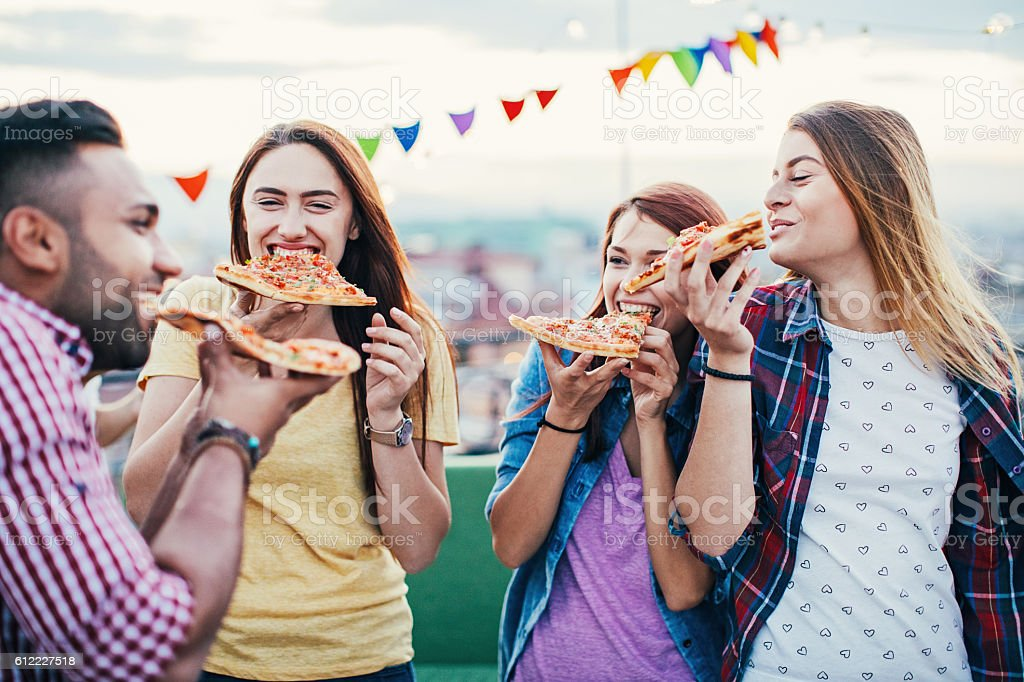 Young people eating pizza on a rooftop party stock photo