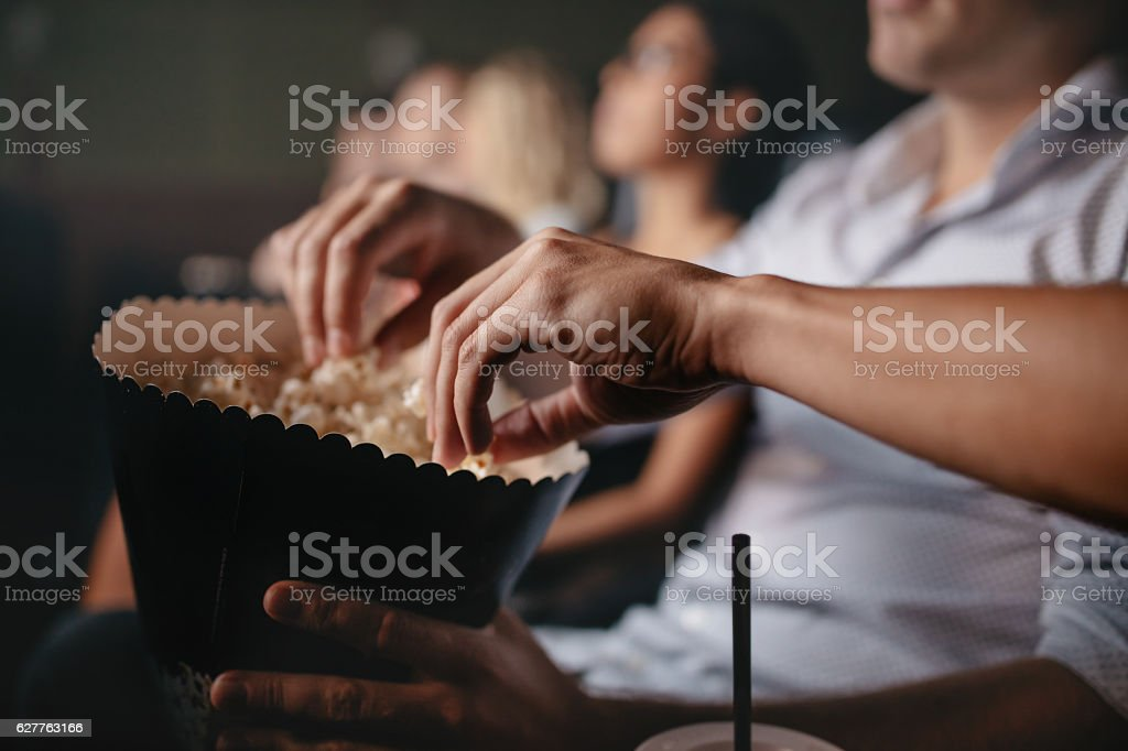 Young people eating popcorn in movie theater stock photo