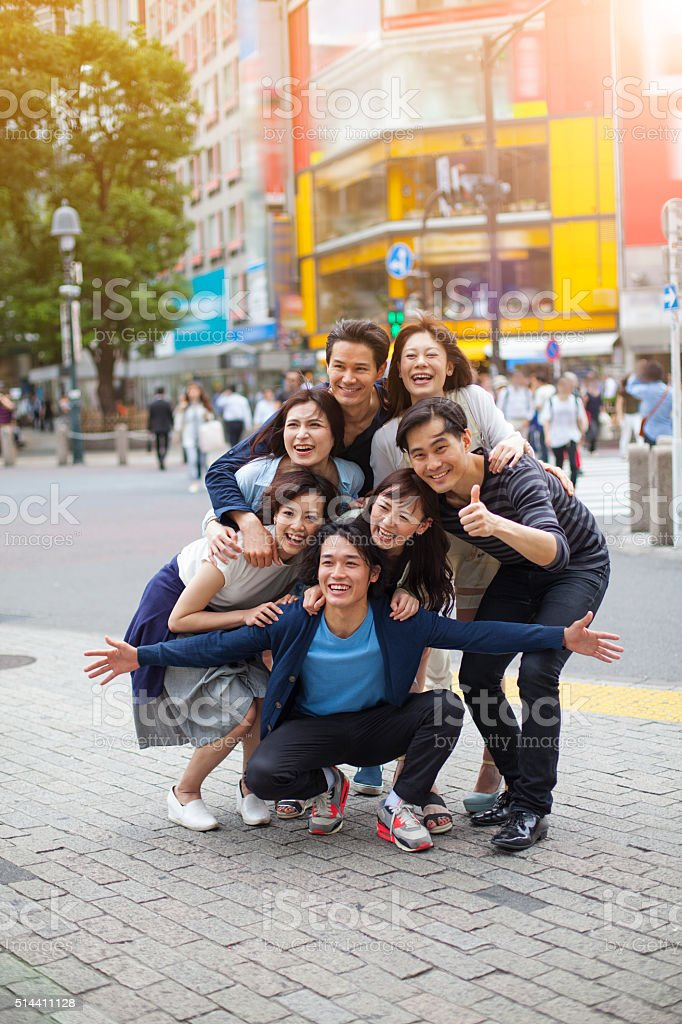 Young people embrace out against cityscape, Tokyo. stock photo