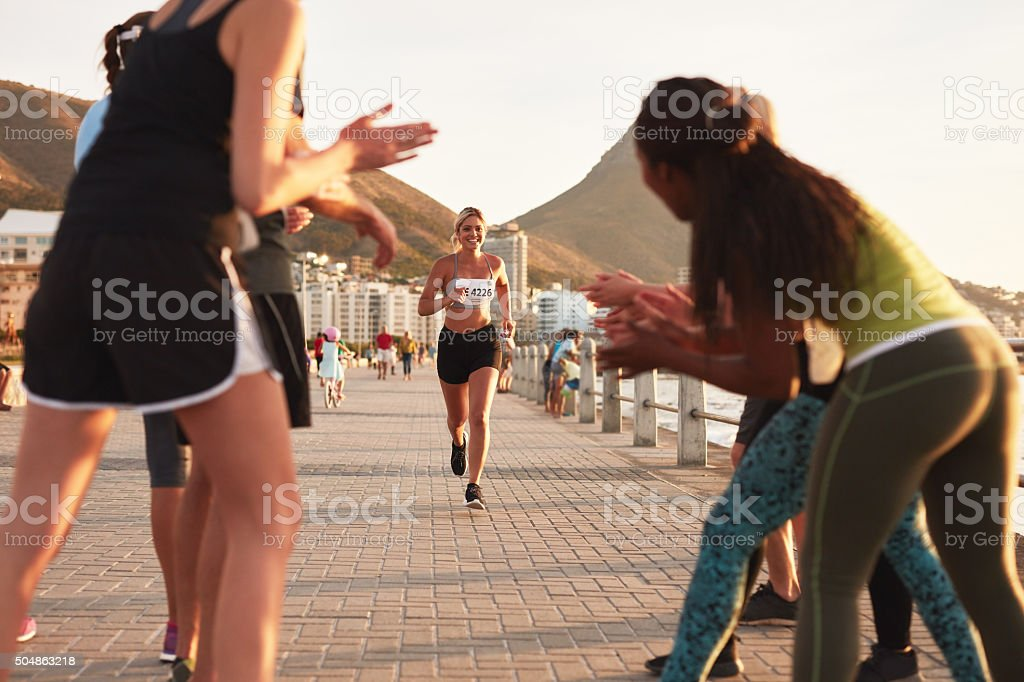 Young people encouraging race runners stock photo