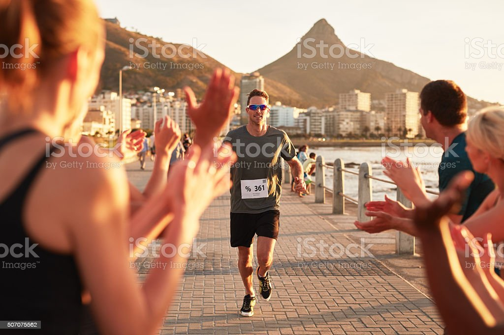 Young people encouraging runners at finish line stock photo