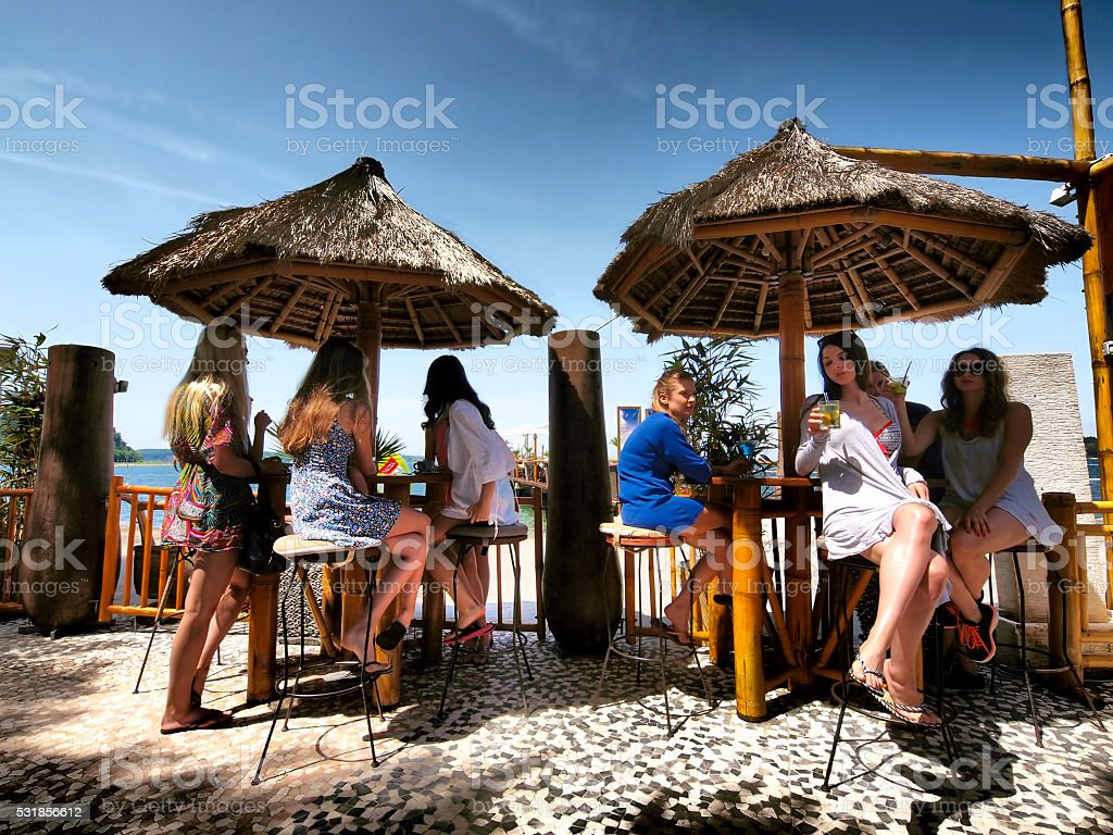 young people enjoy drinks at the beach stock photo