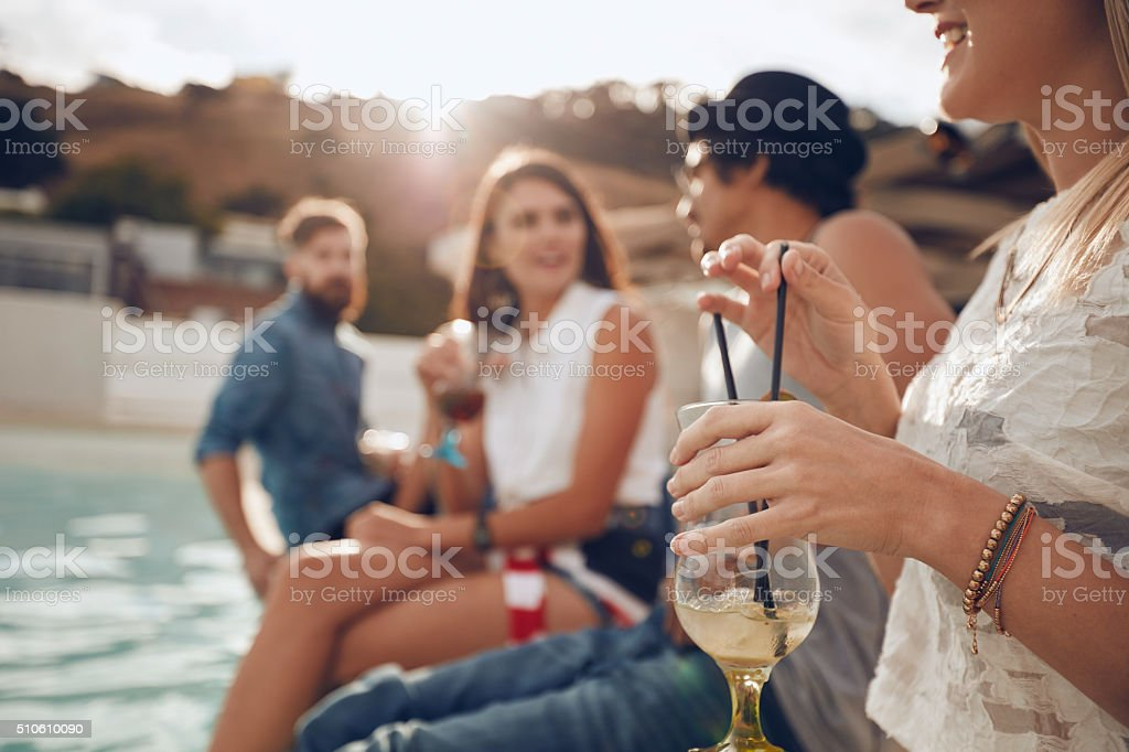 Young people enjoying a cocktail poolside party stock photo