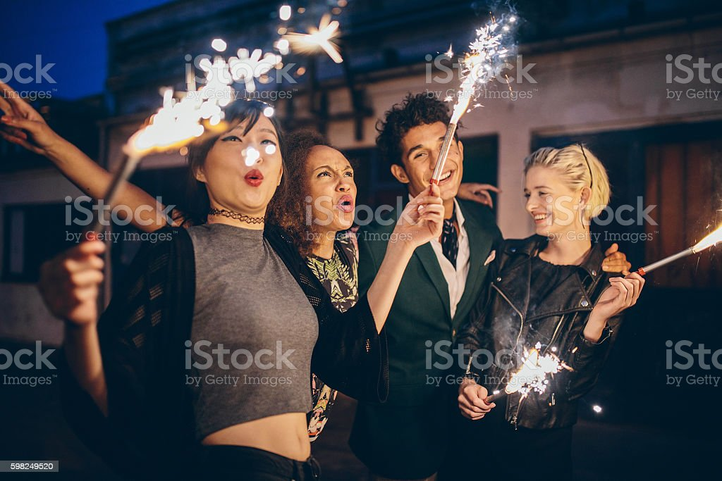 Young people enjoying new years eve with fireworks stock photo