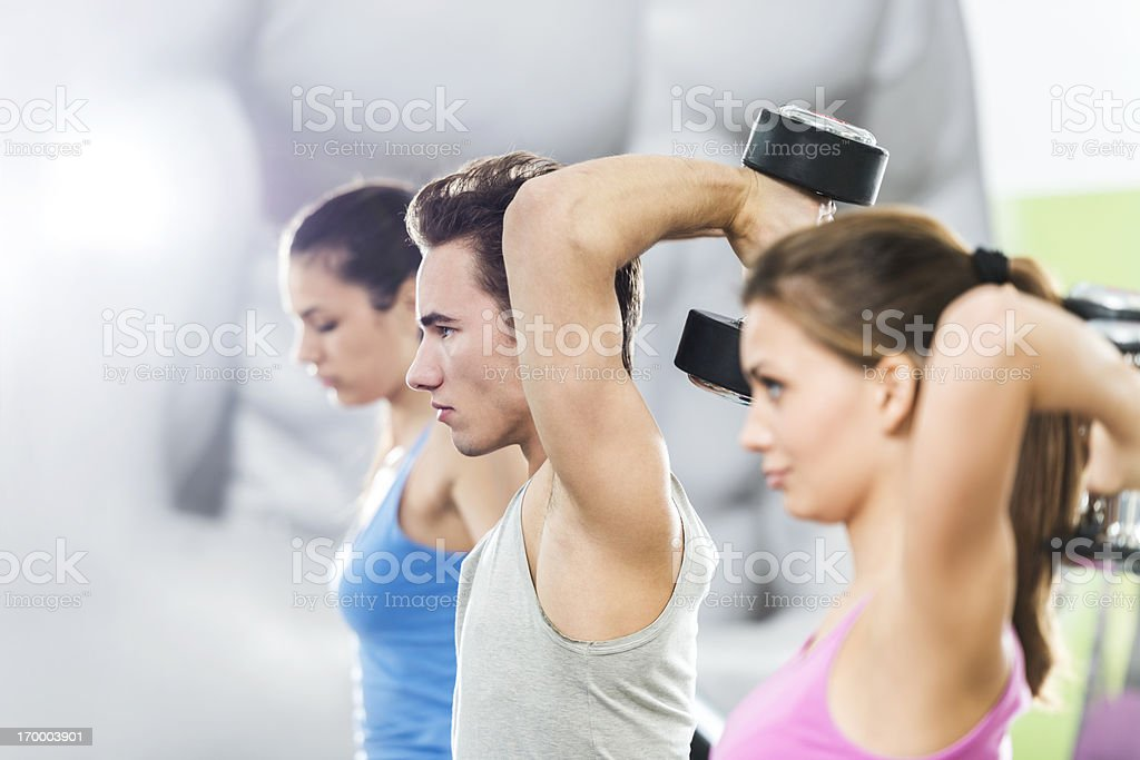 Young people exercising with dumbbells in a gym. royalty-free stock photo
