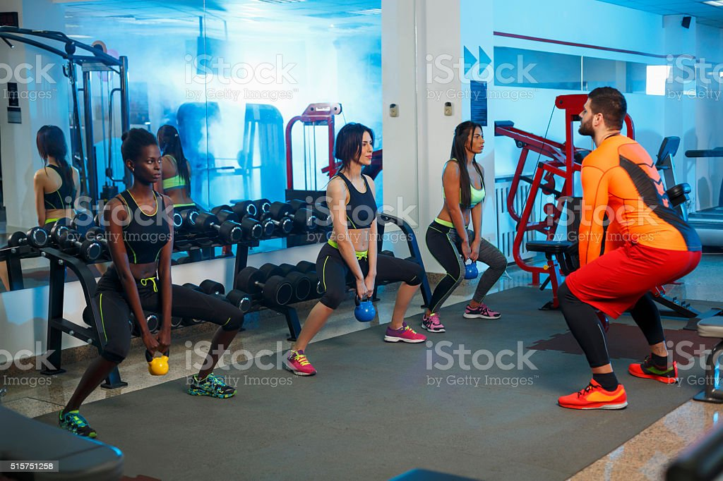 Young people exercising with Kettlebell in a gym  Sports training stock photo
