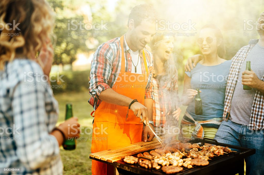 Young people grilling outdoors stock photo