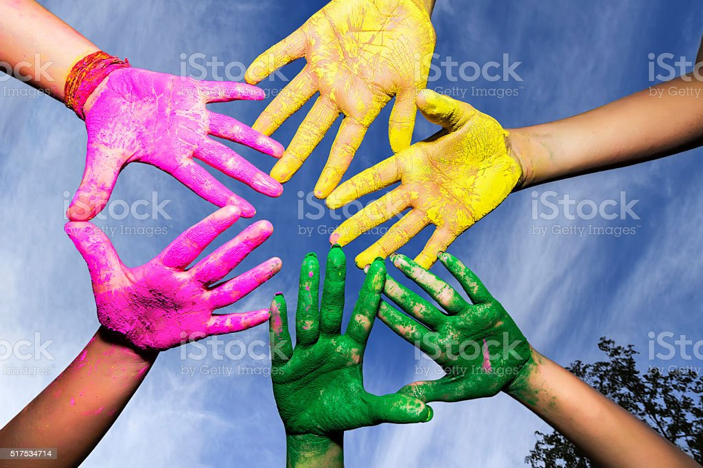 Young people hands covered in Holi Colors under blue sky stock photo