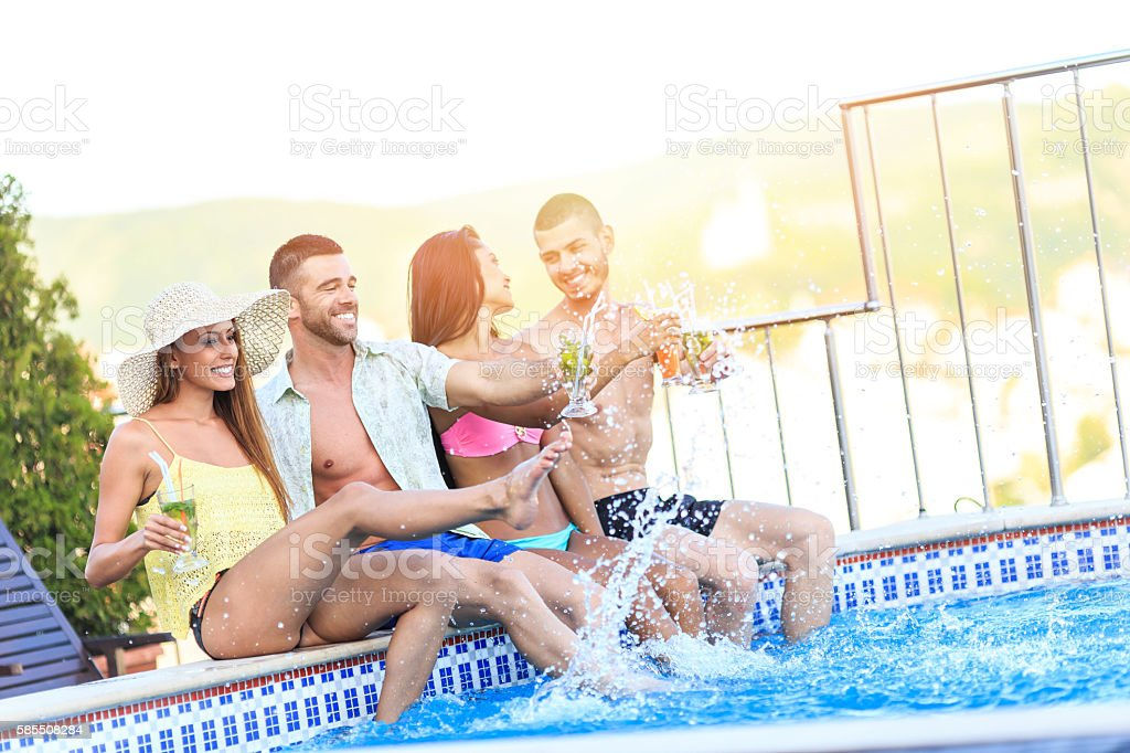 Young people having fun and drinking cocktails at swimming pool stock photo