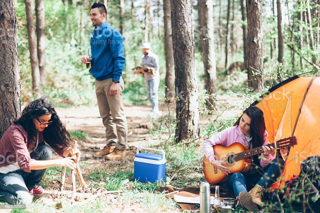 Young people having fun and playing guitar in forest stock photo