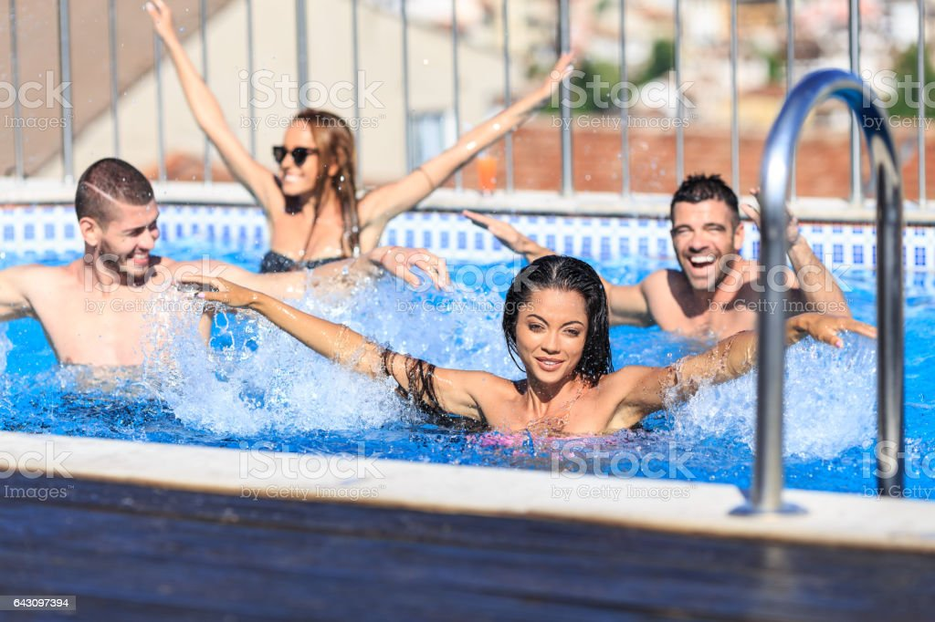 Young people having fun in swimming pool stock photo