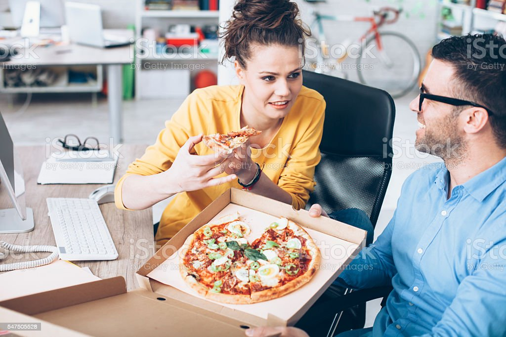 Young people having lunch break at workplace stock photo