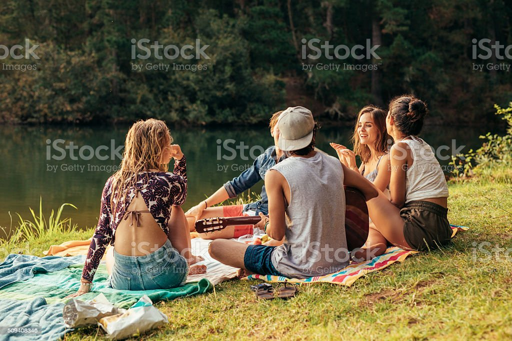 Young people having picnic near a lake stock photo