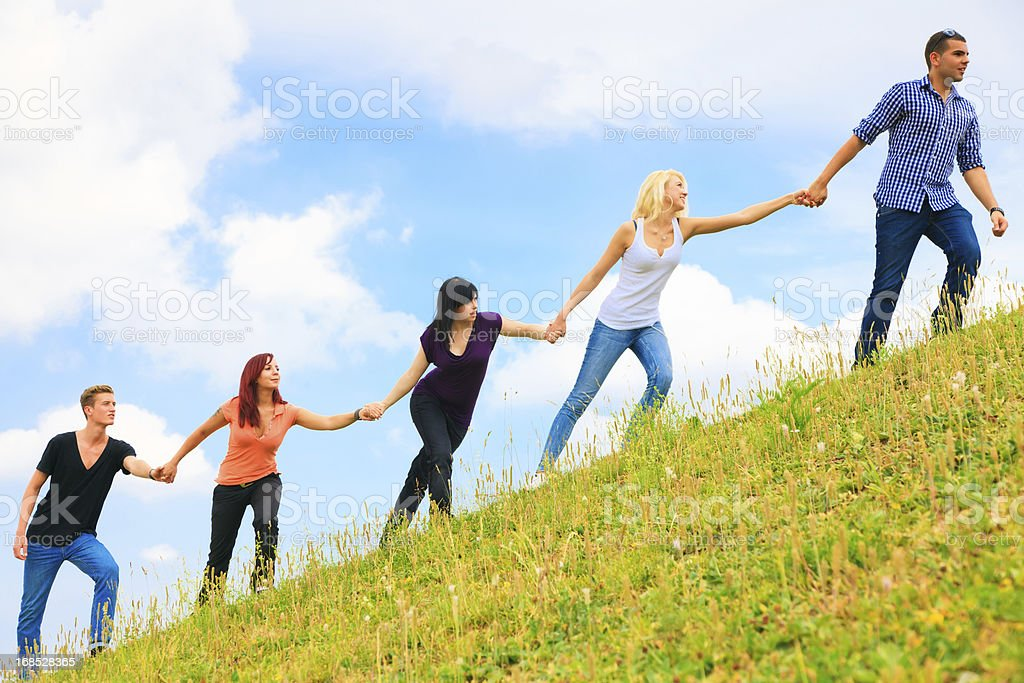 young people helping each other climb a hill stock photo