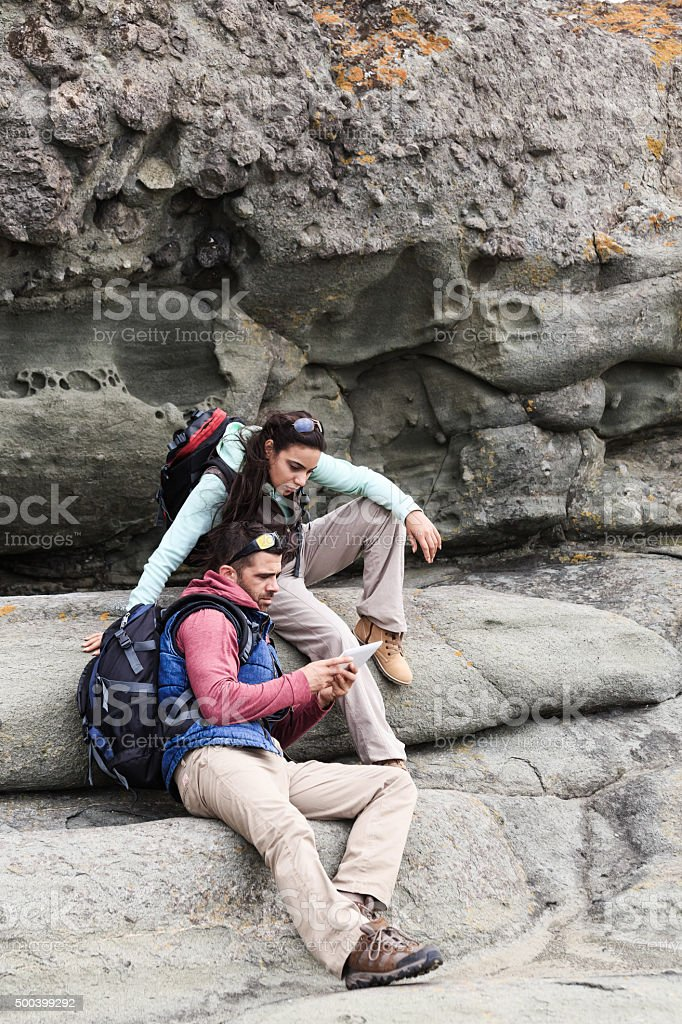 Young people hiking looking map on the rocks stock photo