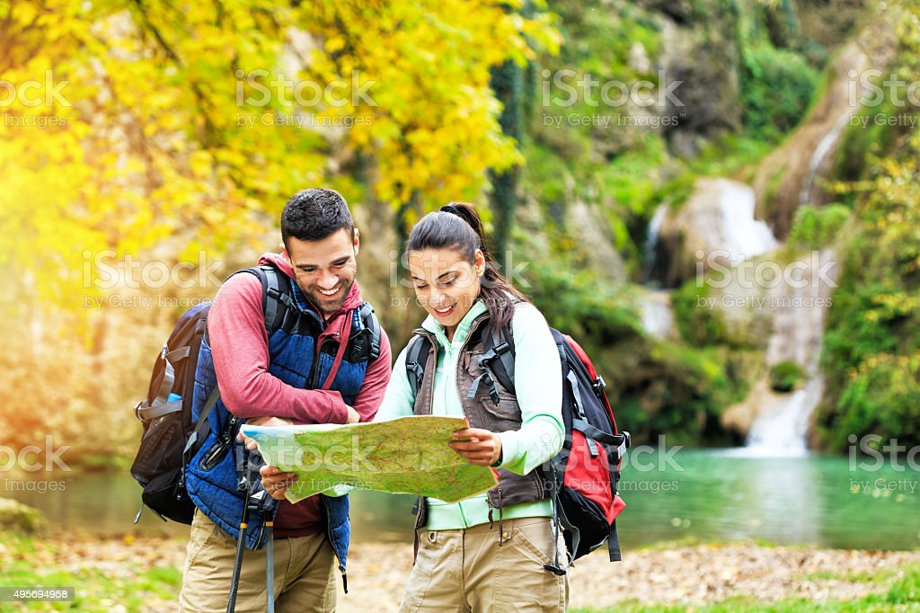 Young people hiking reading the map stock photo