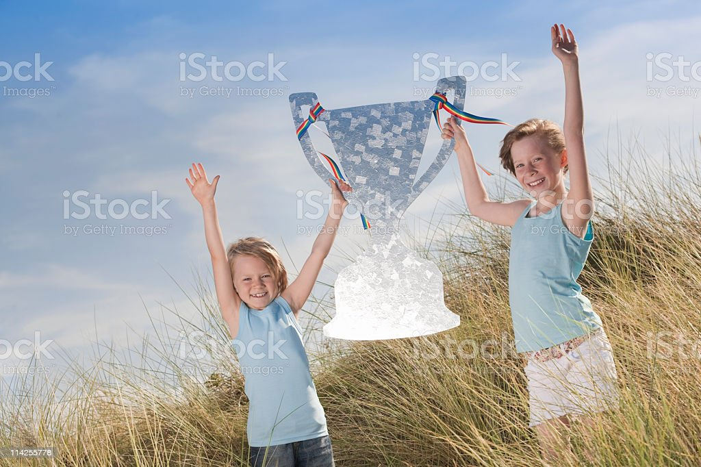 Young people holding up the winning trophy (XXL) stock photo