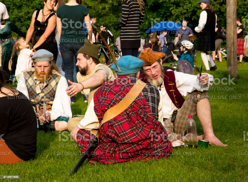 Young people in costumes of Scotland communicate outdoors stock photo