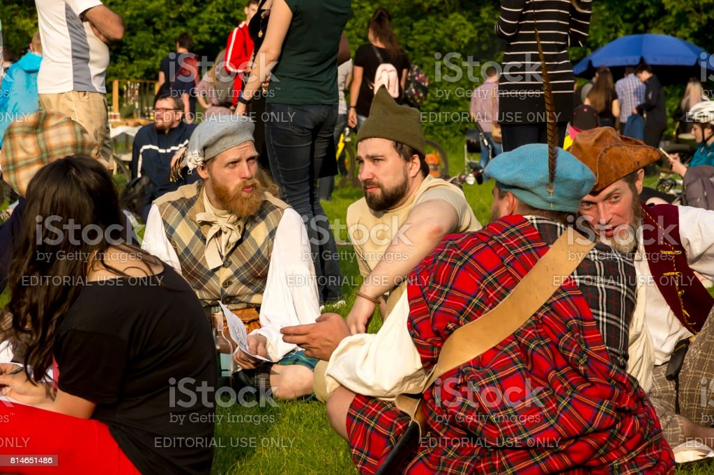 Young people in different costumes of Scotland communicate stock photo
