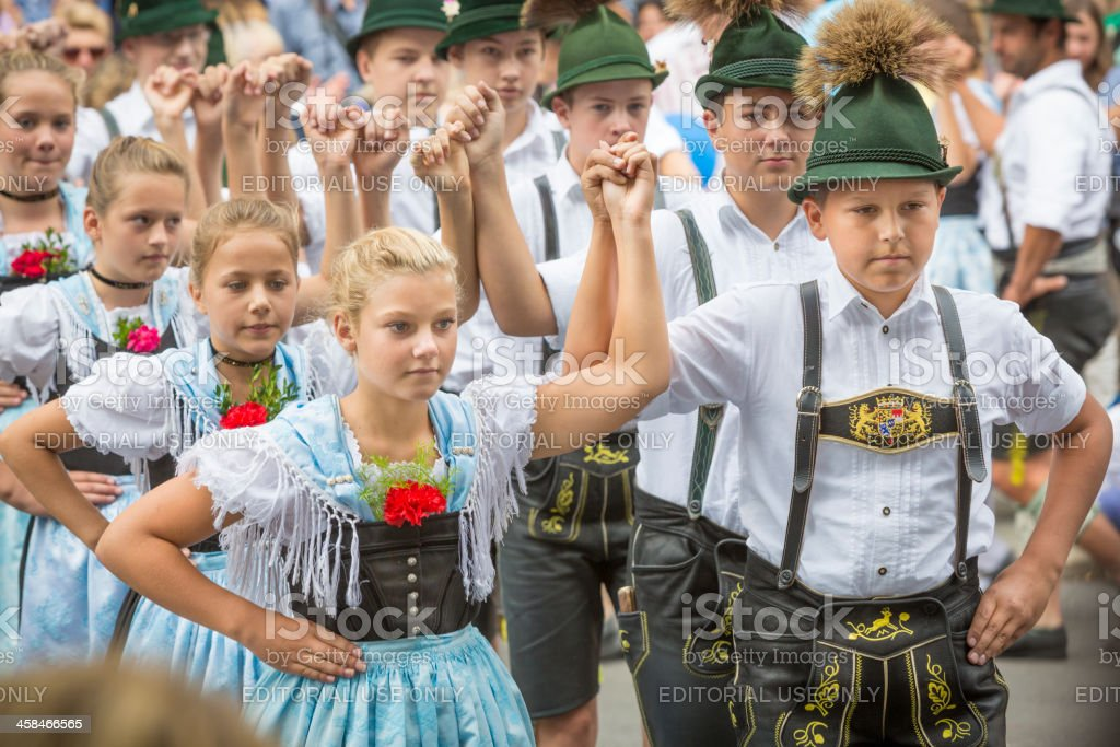 Young people in Dirndl and Leather Trousers performing Bavarian stock photo