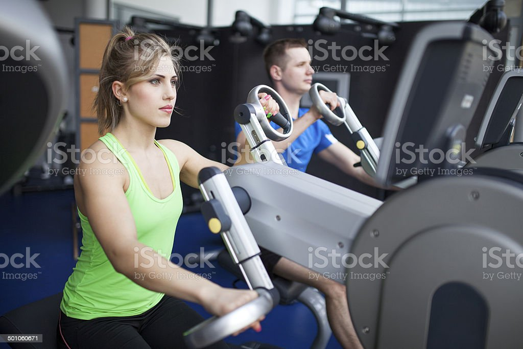 Young people in gym - arms training machine stock photo