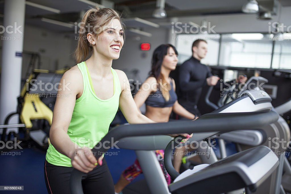 Young people in gym - step machine, treadmill stock photo