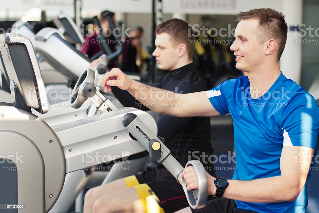 Young people in gym using arms training machine stock photo